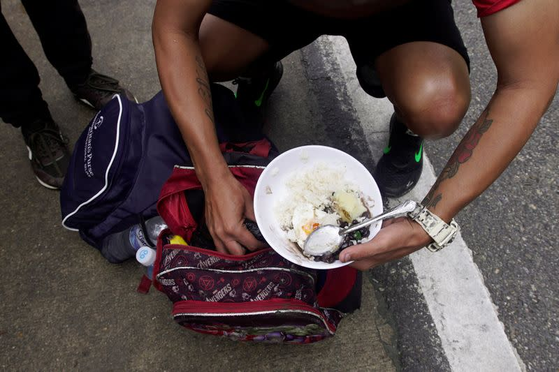 A Venezuelan migrant receives donated food at a point of care for migrants on Colombian roads in Bucaramanga
