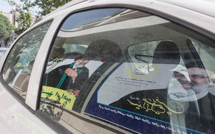 Posters of Ebrahim Raisi are reflected in a car window - Sam Tarling/Sam Tarling for The Telegraph