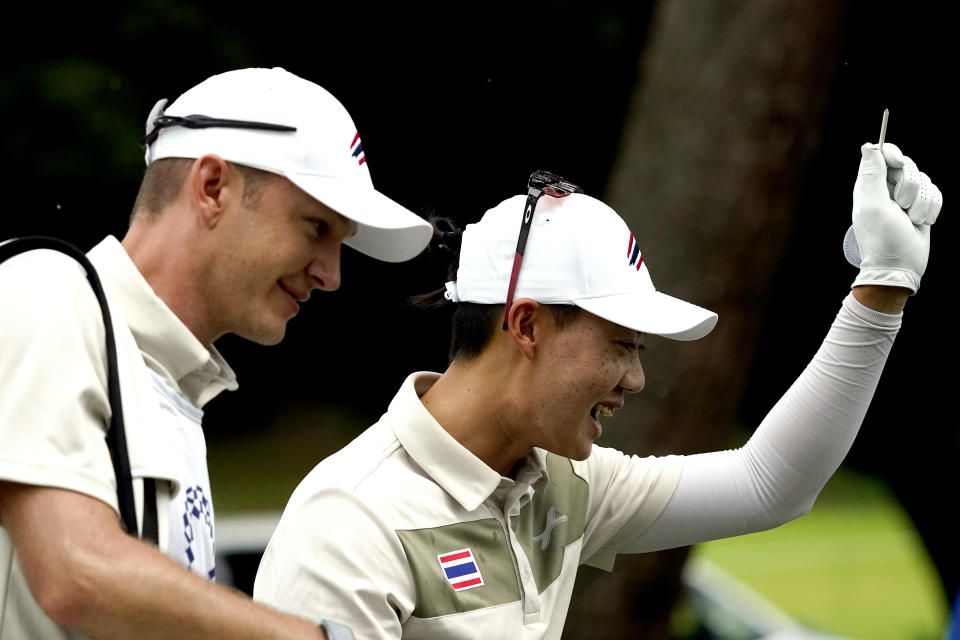 Jazz Janewattananond, of Thailand, smiles after hitting from the 18th tee during the first round for the men's golf event at the 2020 Summer Olympics, Thursday, July 29, 2021, at the Kasumigaseki Country Club in Kawagoe, Japan, (AP Photo/Matt York)