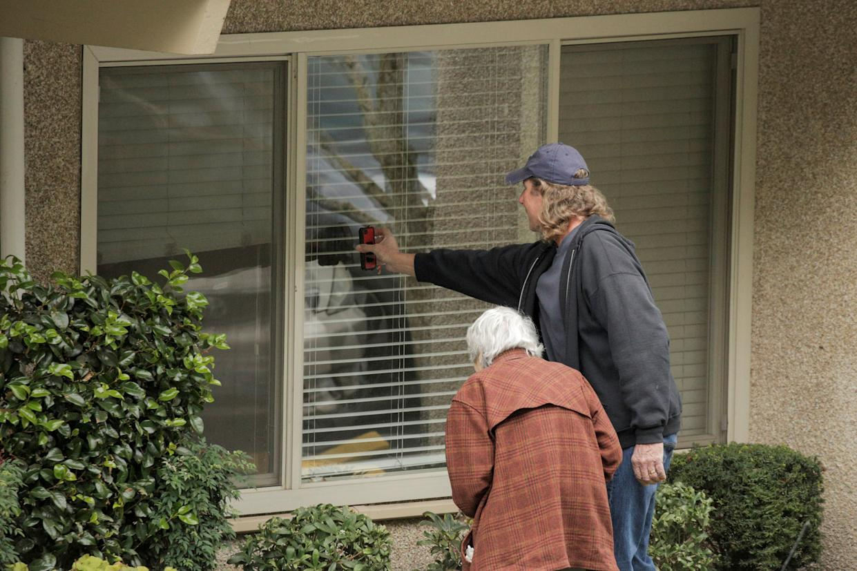 Image: Dorothy Campbell and her son, Charlie Campbell, talk through a window with her husband, Gene Campbell, at the Life Care Center of Kirkland, the long-term care facility linked to several confirmed coronavirus cases in the state, in Kirkland (David Ryder / Reuters)