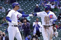 Chicago Cubs' Javier Baez, right, greets Matt Duffy outside the dugout after Baez scored on Duffy's sacrifice fly during the third inning of a baseball game against the Pittsburgh Pirates Fon riday, May 7, 2021, in Chicago. (AP Photo/Charles Rex Arbogast)