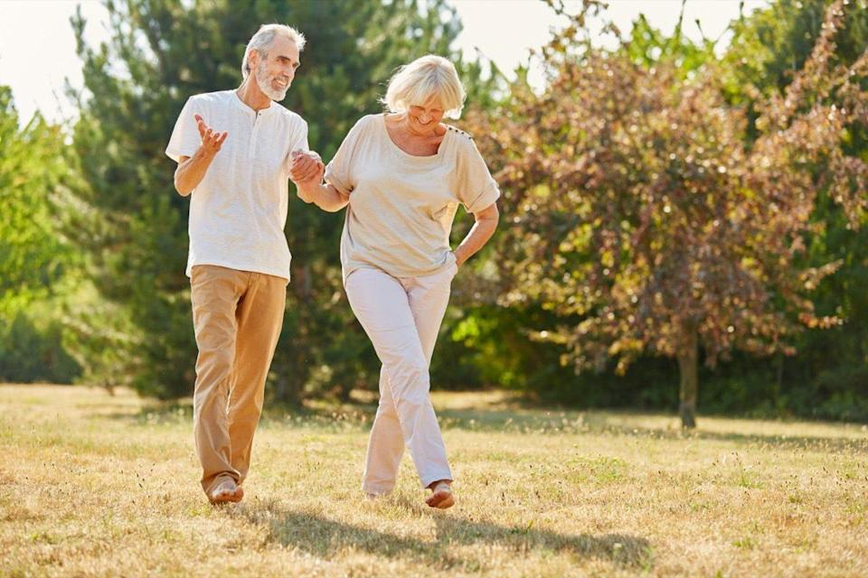 Mature couple holding hands on a walk in the park in summer