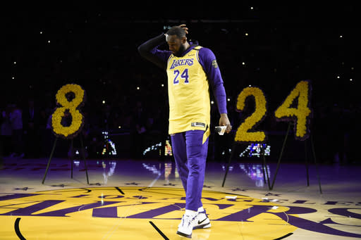 Los Angeles Lakers forward LeBron James looks down while speaking to the crowd in remembrance of Kobe Bryant, prior to the team's NBA basketball game against the Portland Trail Blazers in Los Angeles, Friday, Jan. 31, 2020. (AP Photo/Kelvin Kuo)