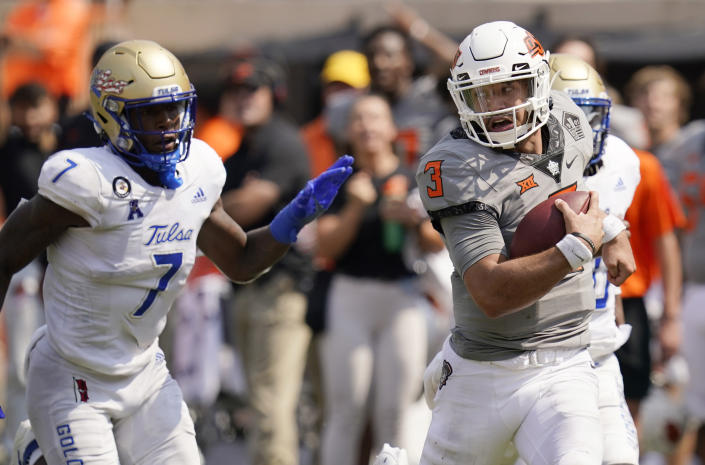 Oklahoma State quarterback Spencer Sanders (3) carries past Tulsa safety TieNeal Martin (7) in the second half of an NCAA college football game, Saturday, Sept. 11, 2021, in Stillwater, Okla. (AP Photo/Sue Ogrocki)