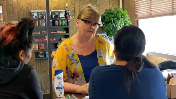 Annette Mason, centre, helps evacuees from Jean Marie River at the front desk of the Snowshoe Inn in Fort Providence, N.W.T. (Travis Burke/CBC - image credit)