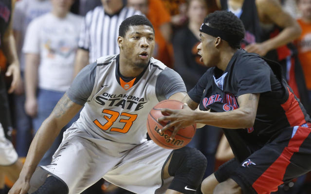 Delaware State guard Kendal Williams (2) drives as Oklahoma State guard Marcus Smart (33) defends in the second half of an NCAA college basketball game in Stillwater, Okla., Tuesday, Dec. 17, 2013. Oklahoma State won 75-43. (AP Photo/Sue Ogrocki)
