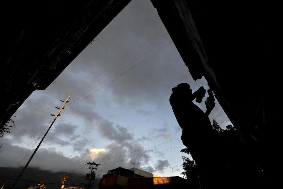 Street artist Wolfgang Salazar is silhouetted against a twilight sky as he works on his most recent art mural, in the Boleita neighborhood of Caracas, Venezuela, Monday, Dec. 28, 2020. Commissioned by a Caracas restaurant, the mural honors triple-jump indoor world record setter Yulimar Rojas, the first Venezuelan honored as athlete of the year by World Athletics. (AP Photo/Matias Delacroix)