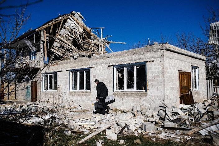 A man carries his belongings as passes by his destroyed home following shelling in the Kuybeshevski area of Donetsk, on November 6, 2014 (AFP Photo/Dimitar Dilkoff)