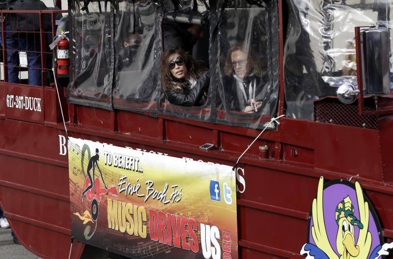 Aerosmith's Steven Tyler, left, and Tom Hamilton look out from a duck boat as they are transported Monday, Nov. 5, 2012 to Boston's Allston neighborhood where they gave a free concert. Aerosmith performed in front of the building which was their home in the early 1970's. (AP Photo/Elise Amendola)