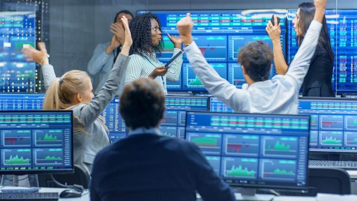 investment analysts celebrating after great trading day