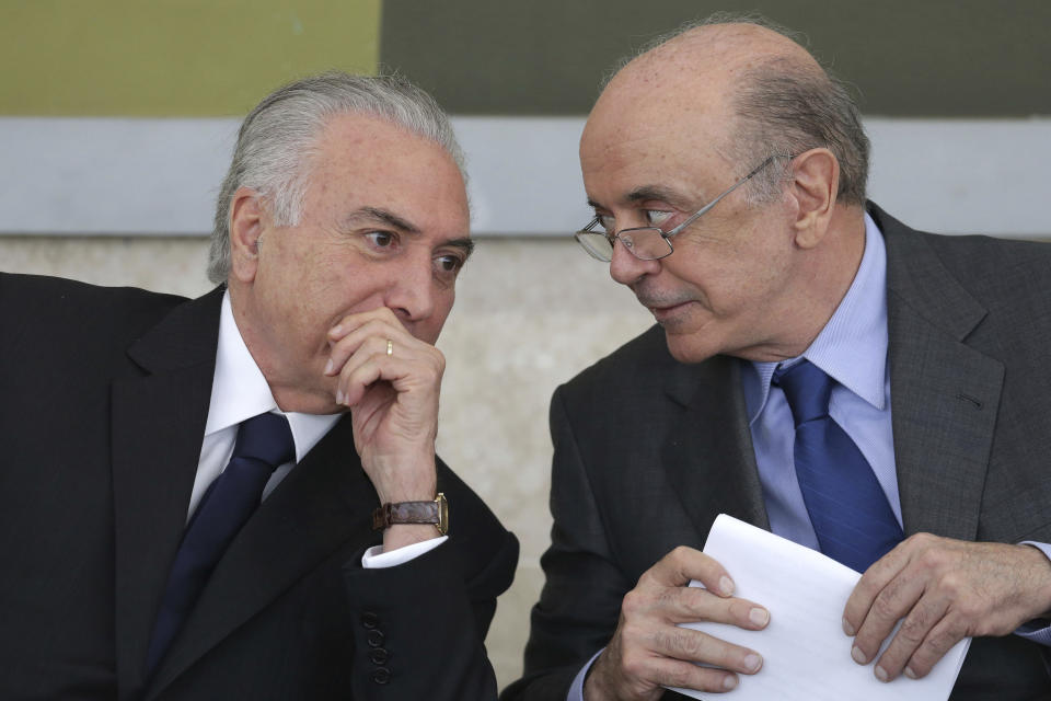 Brazil's President Michel Temer, left, and Foreign Minister Jose Serra attend a decoration ceremony honoring Colombians who helped in the rescue and recovery of the victims of the chartered plane crash involving members of a Brazilian soccer team and a group of journalists, at the Planalto presidential palace, in Brasilia, Brazil, Friday, Dec. 16, 2016. The pilot reported the plane was out of fuel minutes before it slammed into a muddy mountainside near Medellin on Nov. 28, killing all but six of the 77 people on board. (AP Photo/Eraldo Peres)