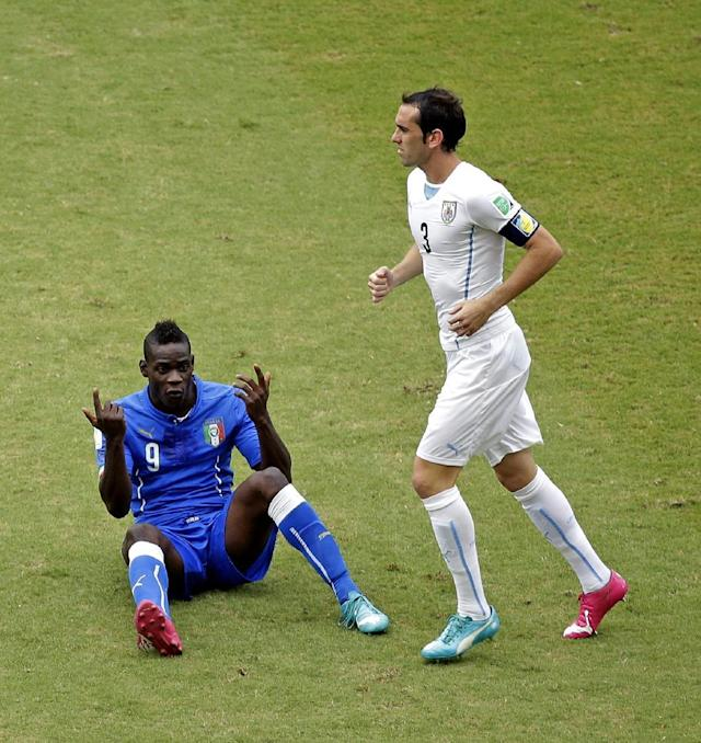 Italy's Mario Balotelli (9) gestures as Uruguay's Diego Godin runs past during the group D World Cup soccer match between Italy and Uruguay at the Arena das Dunas in Natal, Brazil, Tuesday, June 24, 2014. (AP Photo/Hassan Ammar)
