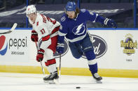 Tampa Bay Lightning defenseman Mikhail Sergachev (98) knocks the puck away from Carolina Hurricanes right wing Andrei Svechnikov (37) during the first period of an NHL hockey game Wednesday, Feb. 24, 2021, in Tampa, Fla. (AP Photo/Chris O'Meara)