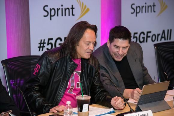 T-Mobile John Legere and Sprint's Marcelo Claure sitting at a table together while looking at a tablet.