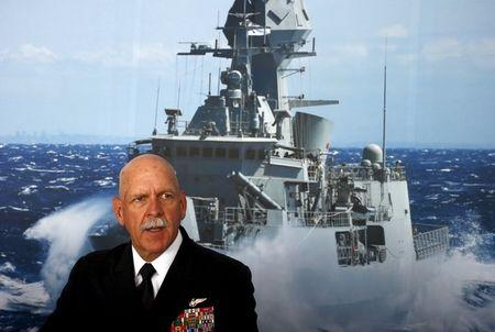 Commander of the US Pacific Fleet Admiral Scott Swift sits in front of a large poster of an Australian Navy frigate as he speaks during a media conference at the 2015 Pacific International Maratime Exposition in Sydney, Australia