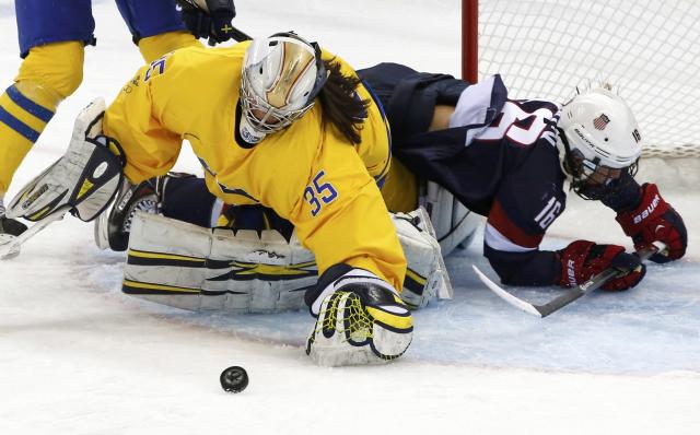 Team USA's Kelli Stack (R) collides with Sweden's goalie Valentina Wallner during the first period of their women's semi-final ice hockey game at the 2014 Sochi Winter Olympics, February 17, 2014. REUTERS/Grigory Dukor (RUSSIA - Tags: OLYMPICS SPORT ICE HOCKEY)