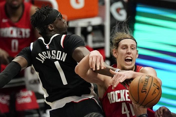 Los Angeles Clippers guard Reggie Jackson, left, and Houston Rockets forward Kelly Olynyk battle for a rebound during the first half of an NBA basketball game Friday, April 9, 2021, in Los Angeles. (AP Photo/Mark J. Terrill)