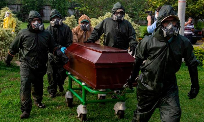 Gravediggers carry a coffin during a funeral at the Jardines del Recuerdo Cemetery in Managua on Friday amid the coronavirus pandemic.