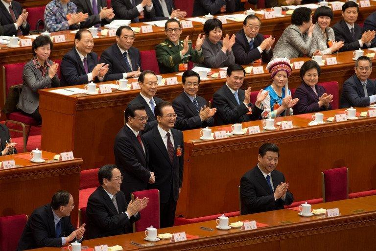 Delegates applaud as China's outgoing premier Wen Jiabao (C-R) shakes hands with newly elected premier Li Keqiang (C-L) next to President Xi Jinping (lower R) during a session of the National People's Congress (NPC) at the Great Hall of the People in Beijing on March 15, 2013. China's parliament installed bureaucrat Li Keqiang as premier in a final step of a landmark power transition