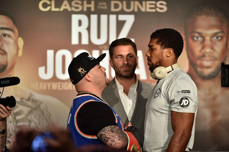 """Mexican-American heavyweight boxing champion Andy Ruiz Jr (L), and British heavyweight boxing challenger Anthony Joshua (R) face each other, as Eddie Hearn (C) looks on during their press conference in Diriyah in the Saudi capital Riyadh, on December 4, 2019, ahead of the upcoming """"Clash on the Dunes"""". - The hotly-anticipated rematch between Ruiz Jr and British challenger Anthony Joshua is scheduled to take place in Diriya, near the Saudi capital on December 7. (Photo by FAYEZ NURELDINE / AFP) (Photo by FAYEZ NURELDINE/AFP via Getty Images)"""