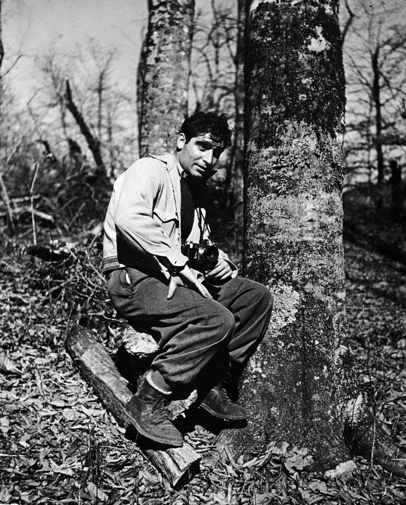 Portrait of Hungarian-born photographer and journalist Robert Capa (1914 - 1954) as he sits on a tree stump and holds a camera, January 6, 1940. (Photo by The LIFE Picture Collection/Getty Images)