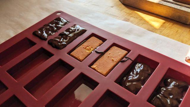 Photo of the candy bar filling in a silicon mold. This photo shows the individual steps: chocolate lined bottom, then placed filling, then topped with more chocolate to set.