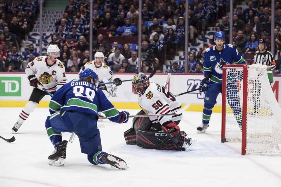 Vancouver Canucks' Adam Gaudette (88) scores against Chicago Blackhawks goalie Corey Crawford (50) during the second period of an NHL hockey game Wednesday, Feb. 12, 2020, in Vancouver, British Columbia. (Darryl Dyck/The Canadian Press via AP)