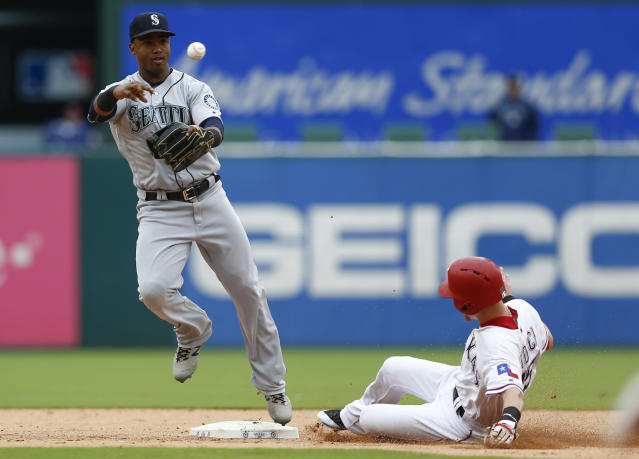 Seattle Mariners shortstop Jean Segura, left, throws to first base after forcing out Texas Rangers' Carlos Tocci, right, turning the first half of a double play on a ball hit by Rangers's Shin-Soo Choo during the fifth inning of a baseball game, Sunday, Sept. 23, 2018, in Arlington, Texas. (AP Photo/Jim Cowsert)