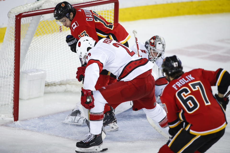 Carolina Hurricanes' Brett Pesce, center, gets the puck away from Calgary Flames' Johnny Gaudreau, left, in front of Hurricanes goalie James Reimer during third-period NHL hockey game action in Calgary, Alberta, Saturday, Dec. 14, 2019. (Jeff McIntosh/The Canadian Press via AP)