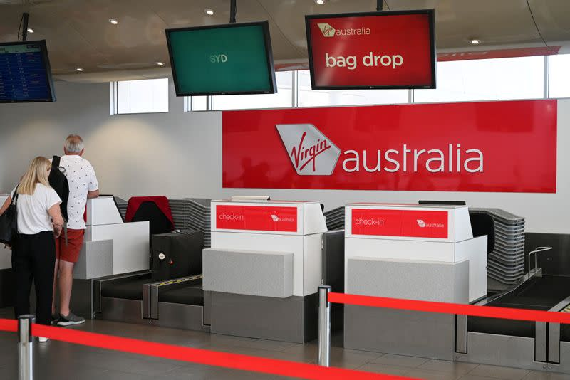 FILE PHOTO: Travelers stand at a Virgin Australia Airlines counter at Kingsford Smith International Airport in Sydney