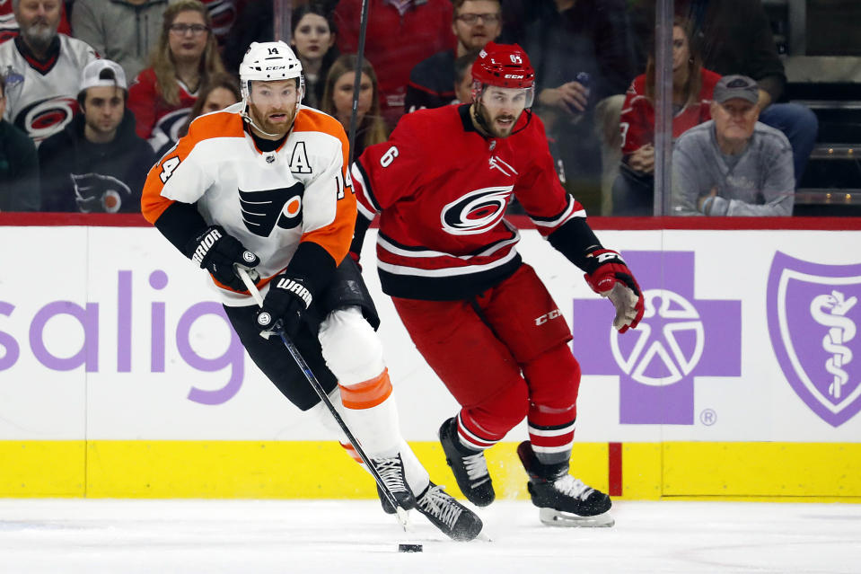 Philadelphia Flyers' Sean Couturier (14) brings the puck up the ice after taking it from Carolina Hurricanes' Joel Edmundson (6) during the first period of an NHL hockey game in Raleigh, N.C., Thursday, Nov. 21, 2019. (AP Photo/Karl B DeBlaker)