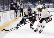 Chicago Blackhawks defenseman Duncan Keith, right, reaches for the puck in front of Columbus Blue Jackets forward Cam Atkinson during the second period of an NHL hockey game in Columbus, Ohio, Monday, April 12, 2021. (AP Photo/Paul Vernon)