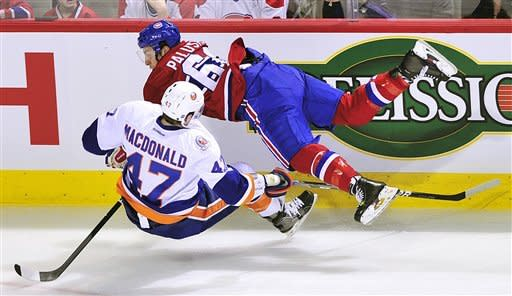 Montreal Canadiens' Aaron Palushaj (60) collides with New York Islanders' Andrew MacDonald (47) during the first period of an NHL hockey game, Saturday, March 17, 2012, in Montreal. (AP Photo/The Canadian Press, Graham Hughes)
