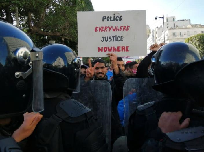 Police officers stand guard as a demonstrator gestures and carries a placard during an anti-government protest in Tunis