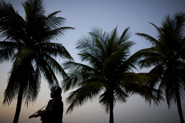 A Brazilian Army soldier in riot gear stands guard at the Barra da Tijuca beach before the auction of the Libra oil field, Brazil's largest single offshore find, in Rio de Janeiro, Brazil, Monday, Oct. 21, 2013. Monday's oil auction is the first in Brazil since the government created new production-sharing agreements. (AP Photo/Felipe Dana)