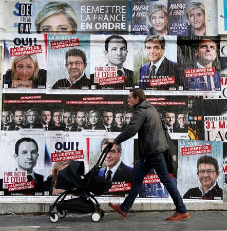 A pedestrian walks past campaign posters for the 2017 French presidential election in Paris