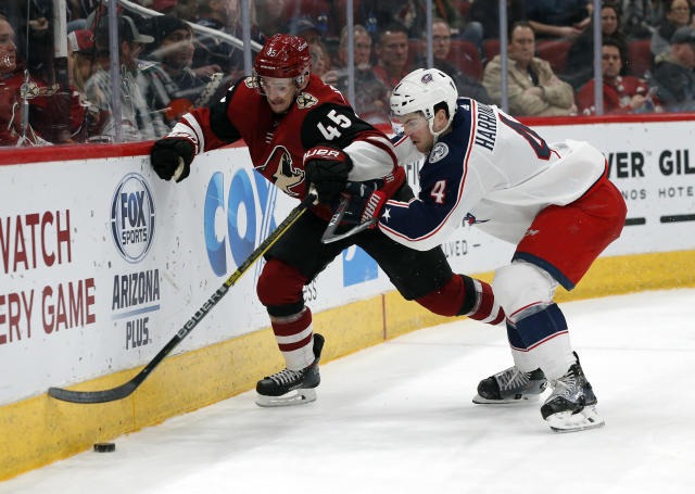Arizona Coyotes right wing Josh Archibald (45) and Columbus Blue Jackets defenseman Scott Harrington battle for the puck in the second period during an NHL hockey game, Thursday, Feb. 7, 2019, in Glendale, Ariz. (AP Photo/Rick Scuteri)