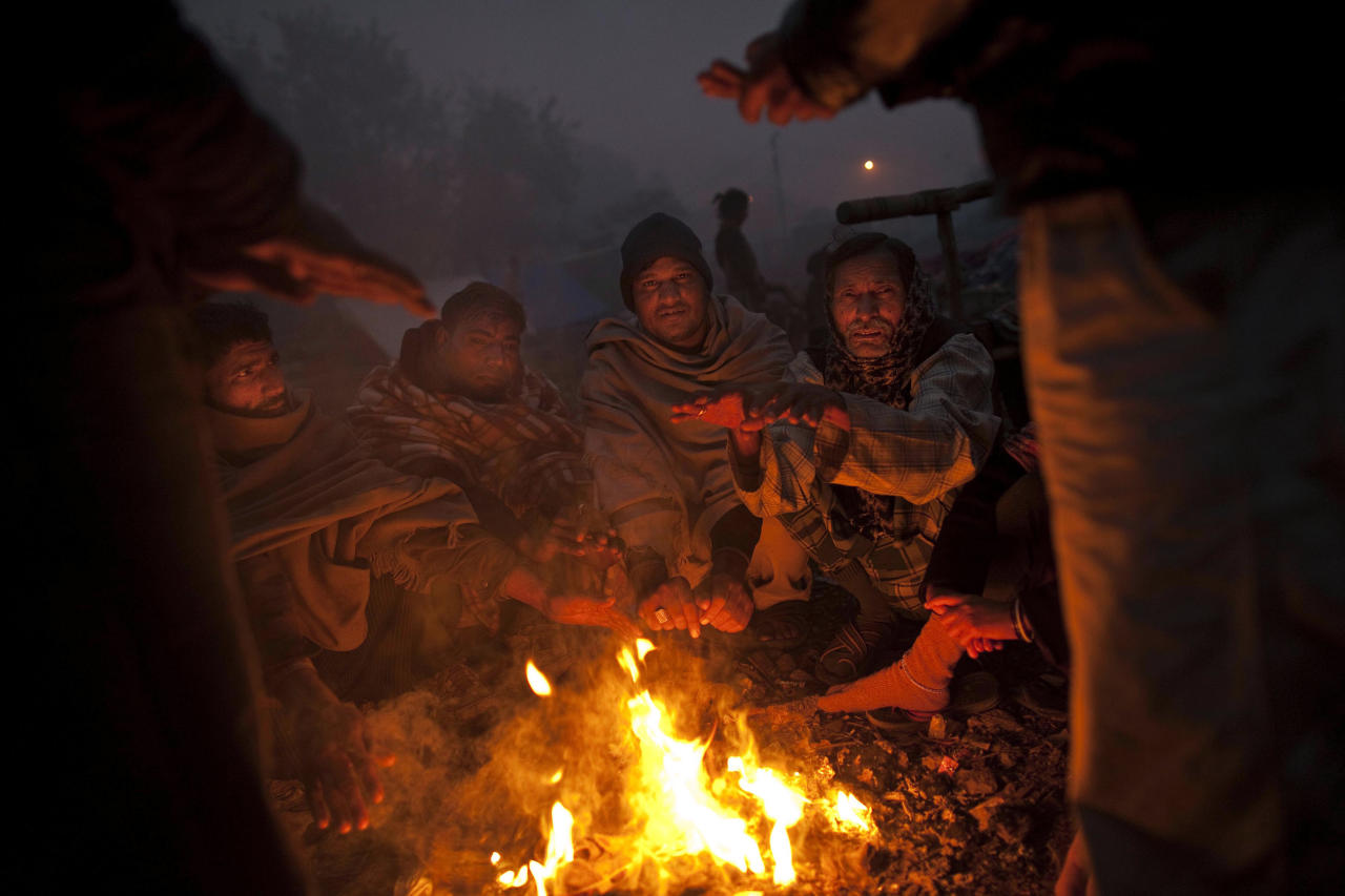 In this photo taken on Jan. 19, 2012, Indian squatters sit together around a fire after waking up at Park No. 2 near Jama Masjid in New Delhi, India. For thousands of people struggling at the bottom of India's working class, the Meena Bazaar parking lot and the handful of places like it scattered across New Delhi are cheap refuges in a city where many migrants can't even afford to rent slum shanties. (AP Photo/Kevin Frayer)