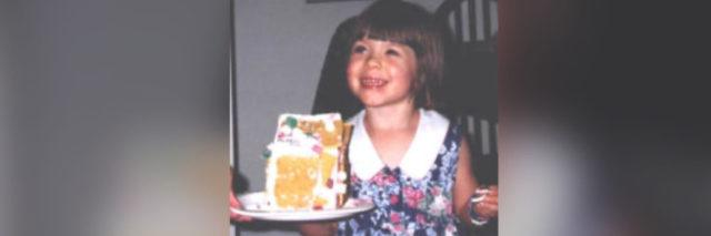 Photo of author as a child smiling in a dress holding a plate with a gingerbread house