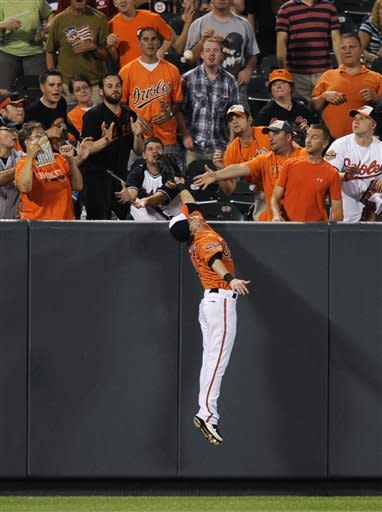 Baltimore Orioles left fielder Nate McLouth reaches in vain for a ball that went for a home run by Kansas City Royals' Alex Gordon during the first inning of a baseball game, Saturday, Aug. 11, 2012, in Baltimore. (AP Photo/Nick Wass)
