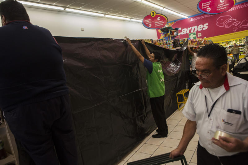 Workers of a supermarket place a black canvas over stacked alcoholic drinks, which the electoral law prohibits selling one day before the general elections, in Guatemala City, Saturday, June 15, 2019. Polls favor former first lady Sandra Torres of the National Unity and Hope party to finish first, but with 19 candidates in the race it is unlikely she will win the absolute majority necessary to avoid a runoff. (AP Photo/Oliver de Ros)