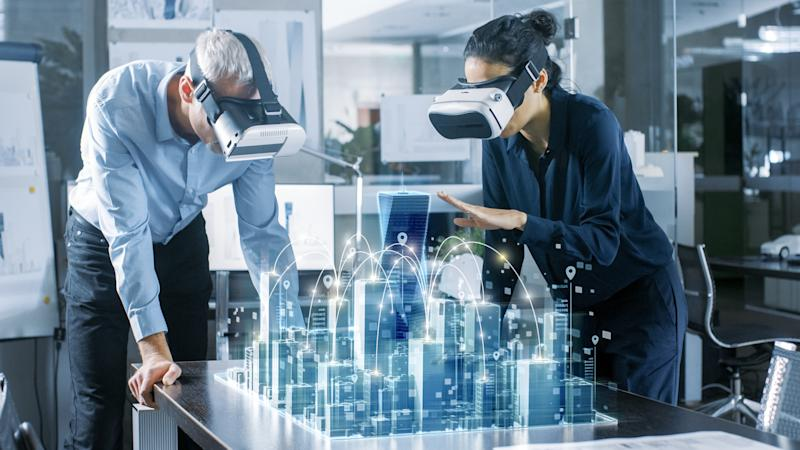 Two people look at a holographic projection of a city.