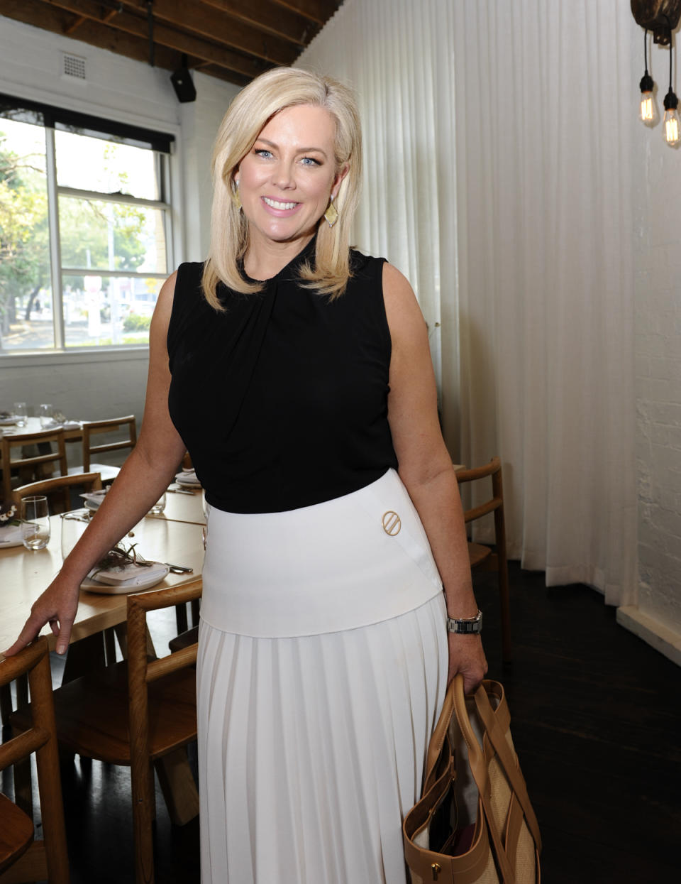Samantha Armytage wears a black top and white skirt at the Jan Logan Merindah Collection Launch on December 03, 2019 in Sydney, Australia.