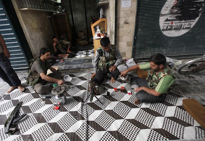 "In this picture taken on Monday September 24, 2012, Free Syrian Army fighters drink tea next to closed shops, at the souk of the old city of Aleppo city, Syria. Fires sparked by clashes between government troops and rebels raged through the medieval marketplace of Aleppo on Saturday, destroying hundreds of shops lining the vaulted passageways where foods, fabrics, perfumes and spices have been sold for centuries, activists said. Arabic writing on the closed shop at right reads:""Aleppo.""(AP Photo/Hussein Malla)"
