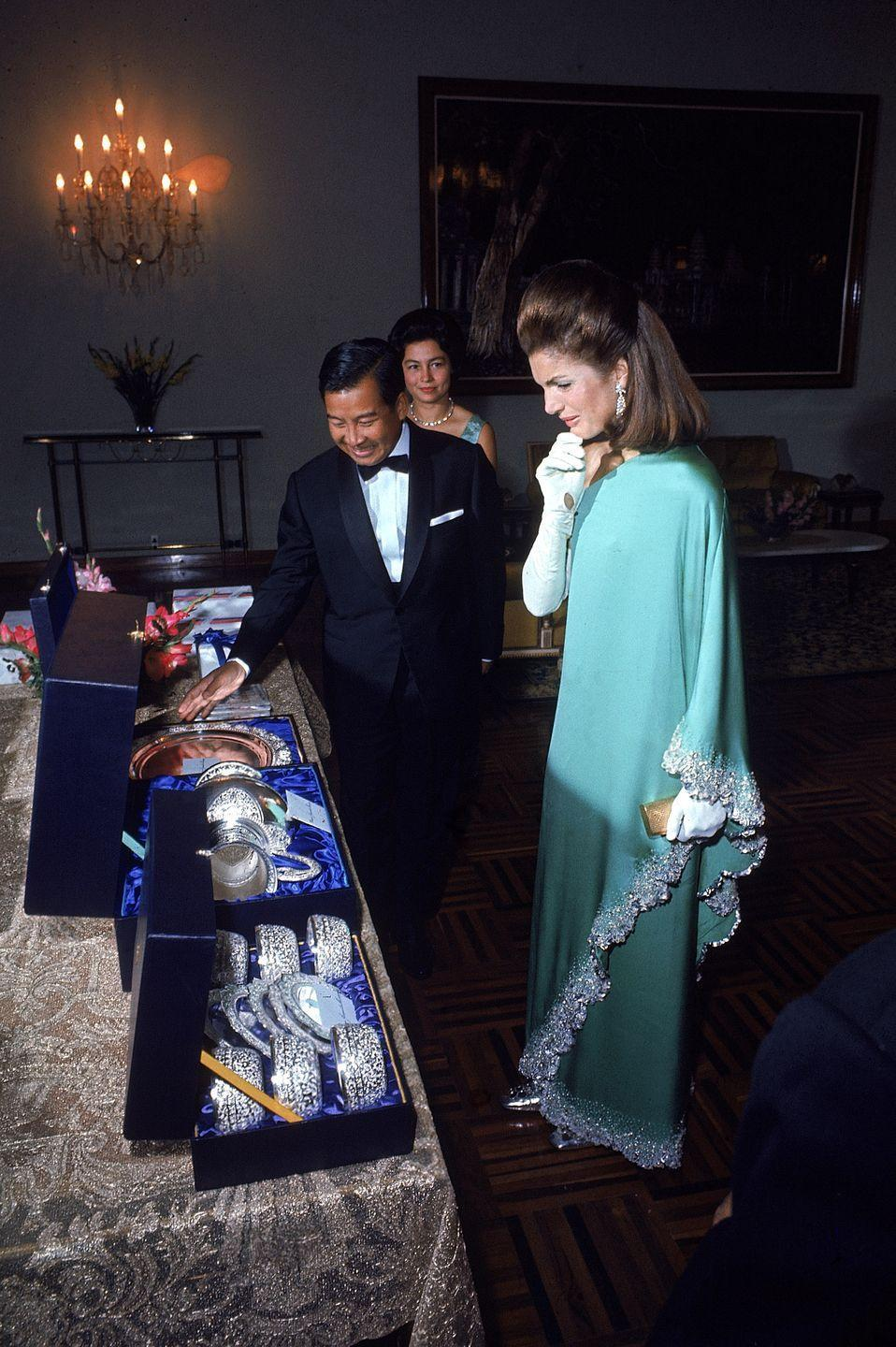 <p>While visiting Cambodia in 1967, Jackie is presented with silver finger bowls by the Cambodian Prince Sihanouk. She wore a green one-shoulder evening gown and white elbow-length gloves for the occasion. </p>