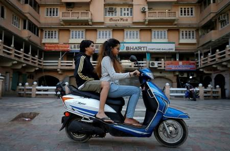 FILE PHOTO: Girls ride an electric scooter in Ahmedabad