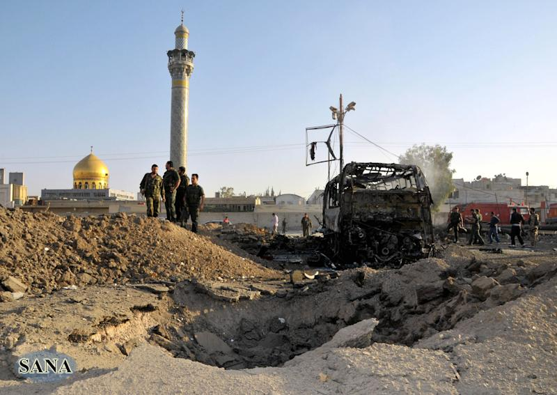 In this photo released by the Syrian official news agency SANA, Syrian soldiers stand at the explosion site where a car bomb exploded near the shrine of Sayyida Zeinab, seen in the background, suburb of Damascus, Syria, Thursday, June 14, 2012. A car bomb exploded Thursday in a Damascus suburb that is home to a popular Shiite Muslim shrine, wounding at least two people, Syria's state-run news agency SANA reported, while activists said regime troops continued shelling rebellious areas in central Homs province. (AP Photo/SANA)