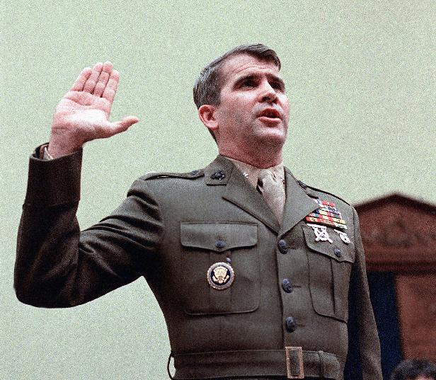 FILE - In this Dec. 18, 1986 file photo, Oliver North is sworn in on Capitol Hill in Washington prior to testifying before the House Foreign Affairs  Committee. Lois Lerner of the IRS joins a diverse roll call of people who have invoked their Fifth Amendment right not to answer lawmakers' questions over the years. North cited his Fifth Amendment rights and refused to answer committee question availing the Iran arms sale. (AP Photo/J. Scott Applewhite, File)