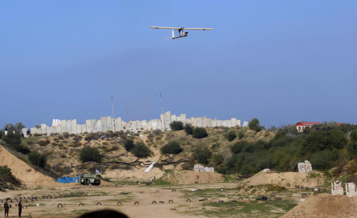 Palestinian militants use a drone to film during a military drill organized by military factions outside Gaza City, Tuesday, Dec. 29, 2020. Palestinian militants in the Gaza Strip fired a salvo of rockets into the Mediterranean Sea on Tuesday as part of a self-styled military drill aimed at preparing for a possible war with Israel. (AP Photo/Adel Hana)
