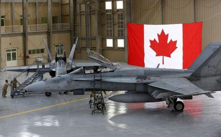 FILE PHOTO: Members of the Canadian Forces push a ladder up to a Canadian F-18 Hornet fighter at a military base in Kuwait
